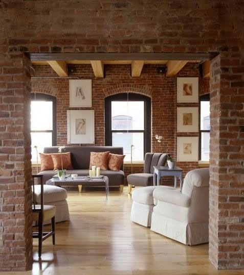 挑高的空间与随意的圆形大坐垫椅配上橘红色砖墙都让这一空间显出一份